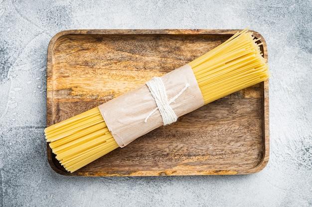 Gedroogde spaghettideegwaren, op houten dienblad, op grijs