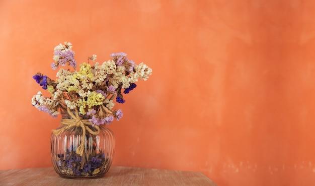Gedroogde statische bloemen in glazen vaas bij de oranje zoldermuur
