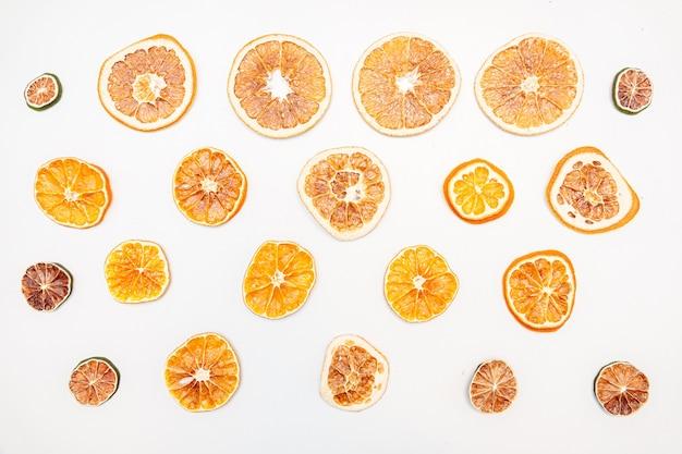 Gedroogde stukjes sinaasappel geïsoleerd op een witte muur