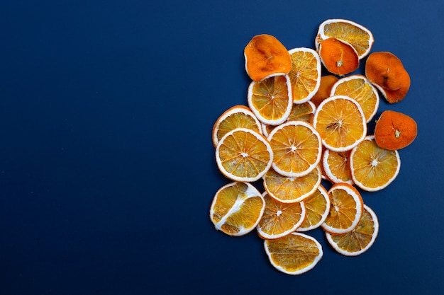 Gedroogde stukjes sinaasappel op blauw