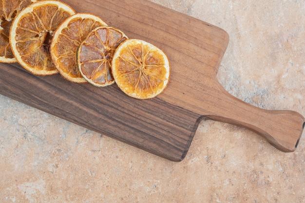Gedroogde stukjes sinaasappel op een houten bord.