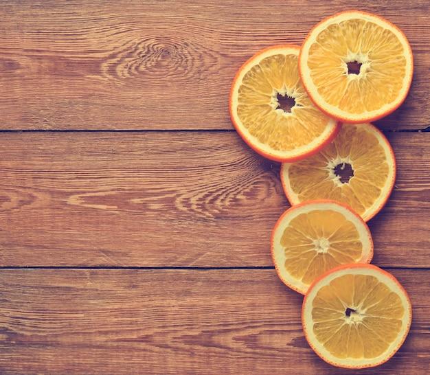 Gedroogde stukjes sinaasappel op een houten oppervlak. bovenaanzicht