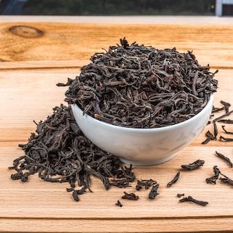 Gedroogde thee wordt gegoten in een keramische kop op een houten plank tafel.