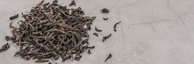Gedroogde thee wordt verspreid over een grijze gestructureerde ruimte gegoten.