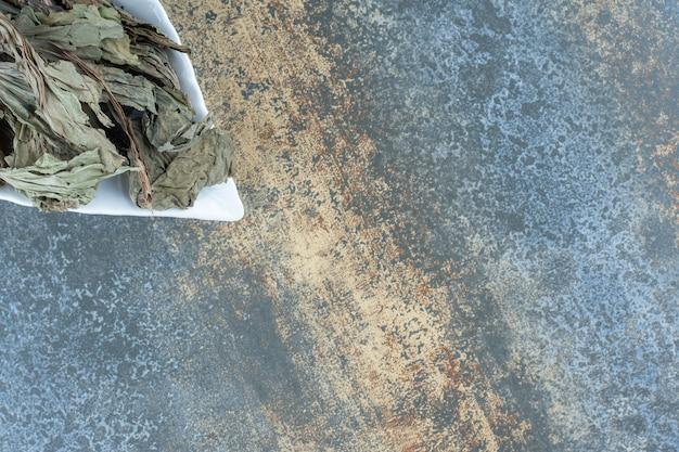 Gedroogde theeblaadjes op bladvormige plaat.