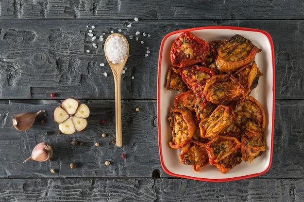 Gedroogde tomaten in een rode en witte kom met zout en peper op een houten tafel. mediterraan tomatenvoorgerecht. vegetarisch eten.