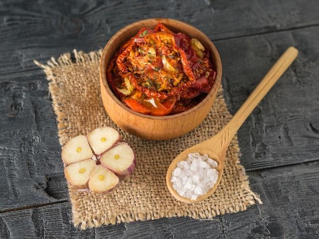 Gedroogde tomaten met knoflook en grof zeezout op een stuk jute. mediterraan tomatenvoorgerecht. vegetarisch eten.
