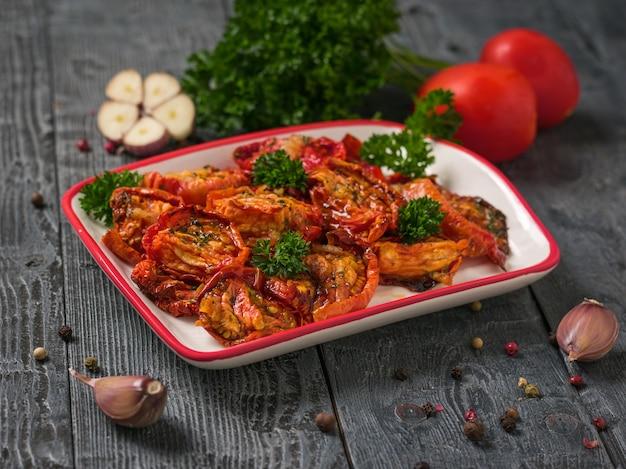Gedroogde tomaten met knoflook en peterselie op een houten tafel. mediterraan tomatenvoorgerecht. vegetarisch eten.