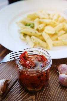Gedroogde tomaten met kruiden in olijfolie, in een glazen pot op een houten tafel.