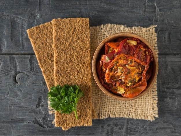 Gedroogde tomaten met toast en peterselie op een stuk jute. mediterraan tomatenvoorgerecht. vegetarisch eten. plat leggen.