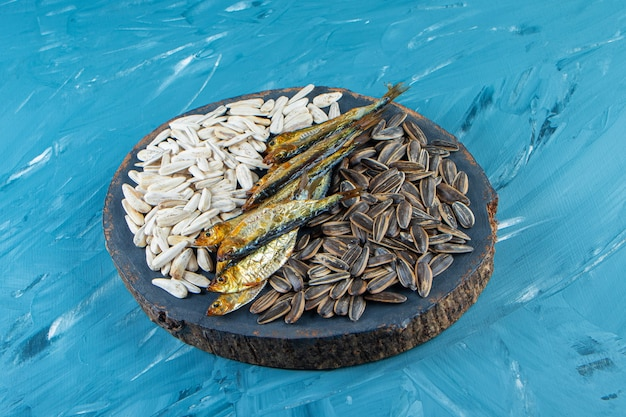 Gedroogde vis en pit op een bord, op het blauwe oppervlak.
