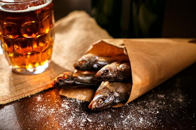 Gedroogde vis en vintage glas bier op een zwarte ondergrond