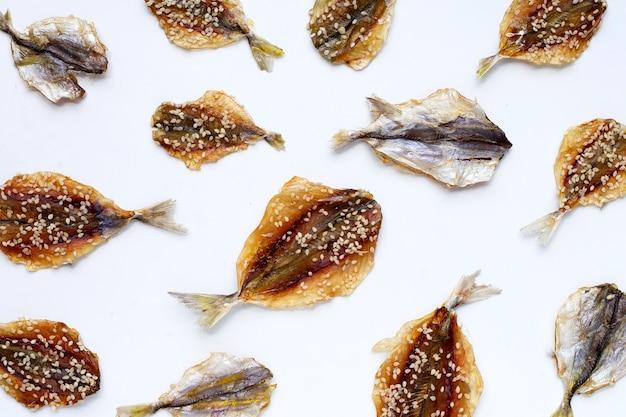 Gedroogde vis met sesamzaadjes op witte achtergrond.
