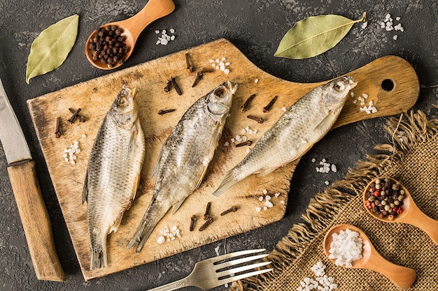 Gedroogde vis met zout en peper op snijplank