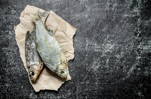 Gedroogde vis op papier. op zwarte rustieke achtergrond
