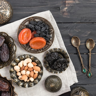Gedroogde vruchten en noten; dadels voor ramadan met lepels over het houten bureau