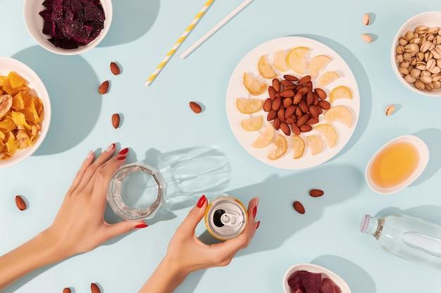 Gedroogde vruchten en noten met saus op blauwe achtergrond met dames handen