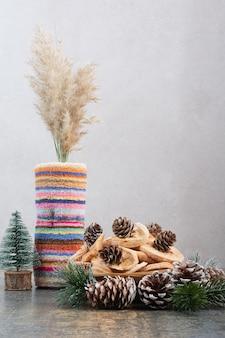 Gedroogde vruchten en pinecones in houten kom op marmeren achtergrond. foto van hoge kwaliteit