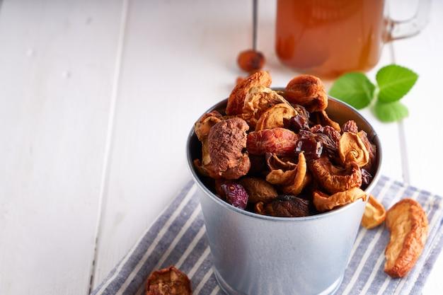 Gedroogde vruchten en zelfgemaakte compote van gedroogde vruchten in een pot op een lichte tafel.