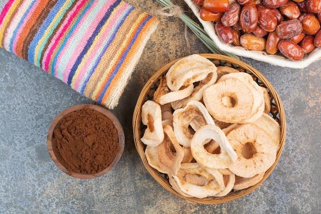 Gedroogde vruchten met cacaopoeder in houten kom op marmeren achtergrond. foto van hoge kwaliteit