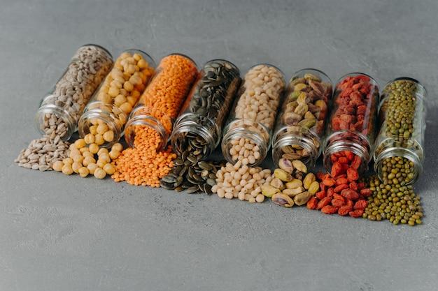 Gedroogde zaden, bonen en verschillende granen uitgegoten uit glazen flessen