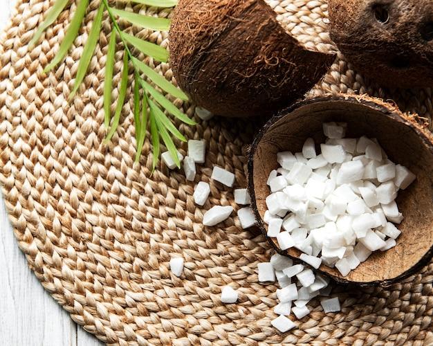 Gedroogde zoete kokosnoot blokjes in kom op houten tafel achtergrond.