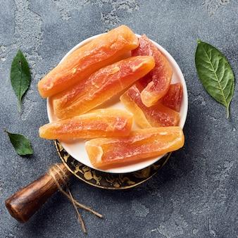 Gedroogde zoete papajastokken. gekonfijte vruchten op grijze achtergrond