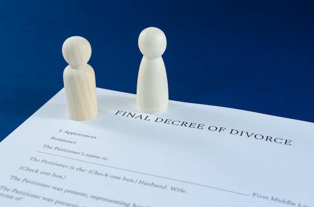 Gedrukt echtscheidingsbesluit met houten beeldjes van man en vrouw die apart staan in een conceptueel beeld voor echtscheiding. over blauwe ruimte.