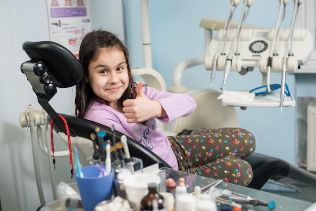 Geduldig meisje duimen opdagen op het kantoor van de tandheelkundige kliniek