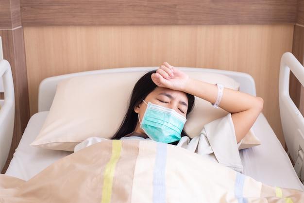 Geduldige aziatische vrouwen met hoofdpijn of migraine ernstig in het ziekenhuis, dengue-koorts
