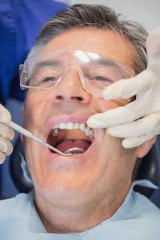 Geduldige mond open en tandarts die onderzoekt