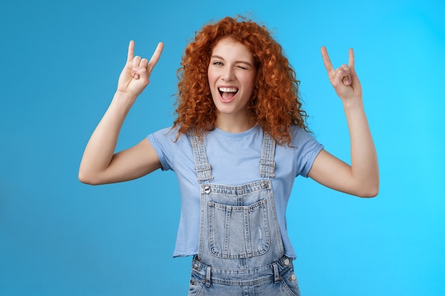 Gedurfd cool brutaal roodharige roodharige meisje krullend natuurlijk kapsel knipogen vreugdevol schreeuwen ja geniet van geweldig feest dansen muziek festival show rock-n-roll heavy metal gebaar veel plezier blauwe achtergrond.