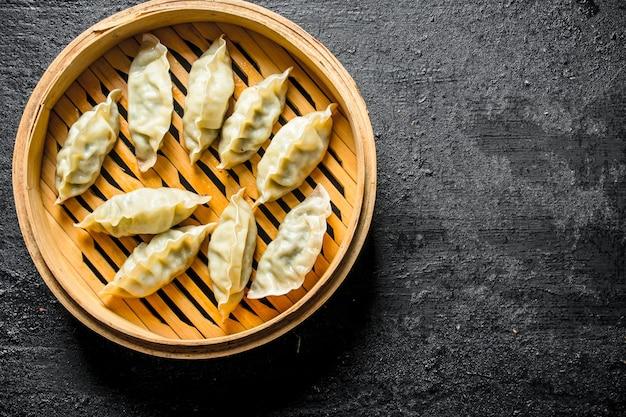 Gedza-dumplings in een bamboestoomboot. op zwarte rustieke achtergrond