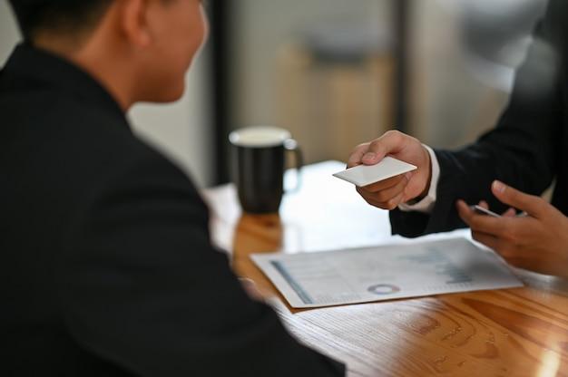 Geef een blanco visitekaartje aan bezoekersclose-up shot met zakelijk gesprek.