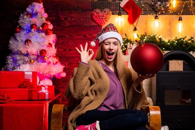Geef een knipoog gek komisch gezicht kerstvrouw houd bom creatieve boom bom emoties mooie vrouw...