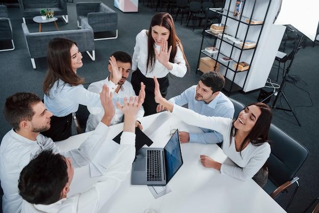 Geef elkaar een high five. bovenaanzicht van kantoorpersoneel in klassieke slijtage zitten in de buurt van de tafel met behulp van laptop en documenten