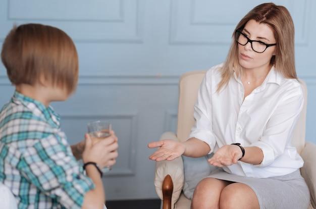 Geef het aan mij. portret van ernstige psycholoog die witte blouse en rok draagt die jongen bekijkt terwijl hij een helpende hand uitstrekt naar tienerpatiënt