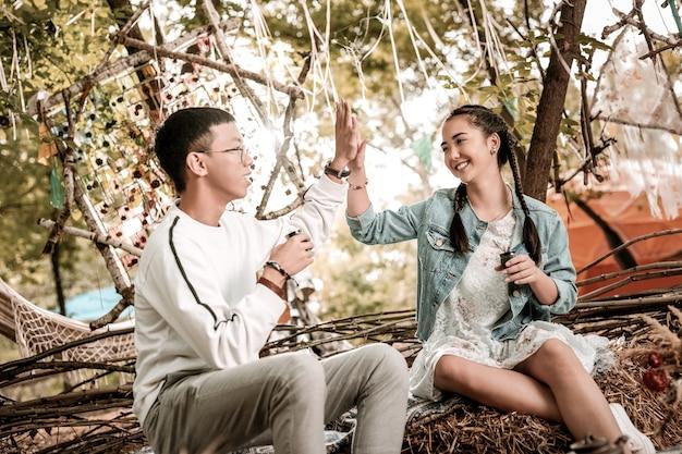 Geef high-five. gelukkig meisje glimlach op haar gezicht te houden terwijl het aanraken van handen met haar vriendje