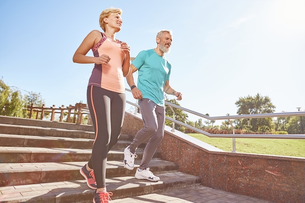 Geef je ochtend een volledige opname van een actief volwassen familiepaar in sportkleding hardlopen