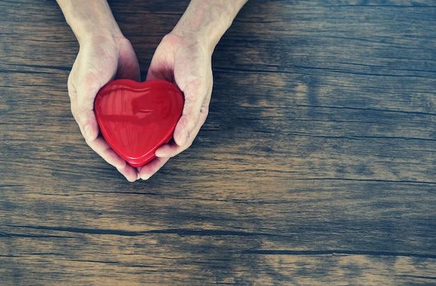 Geef love man die rood hart in handen houdt voor liefde valentines zorgen