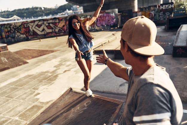 Geef me een hand! mooie jonge vrouw die naar haar vriend probeert te klimmen terwijl ze buiten tijd doorbrengt in het skatepark