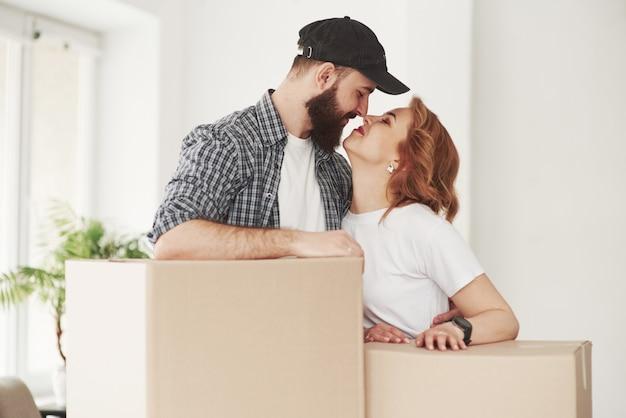 Geef me een kus. gelukkig paar samen in hun nieuwe huis. conceptie van verhuizen