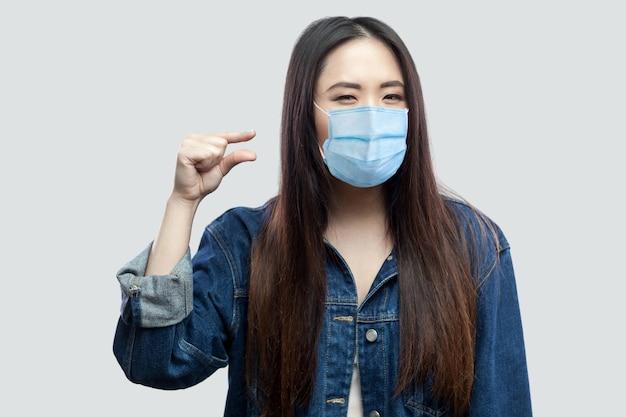 Geef me er nog een paar. portret van een brunette aziatische jonge vrouw met een chirurgisch medisch masker in een casual blauw spijkerjasje dat staat en een klein formaat toont met de hand. studio opname, geïsoleerd op een grijze achtergrond.