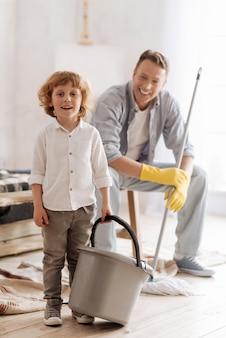 Geef me taken. glimlachende vader die op de achtergrond zit en de wissel in beide handen houdt terwijl hij naar zijn zoon kijkt
