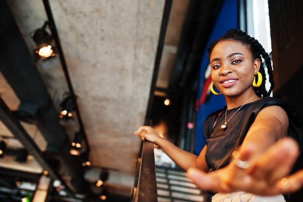 Geef mij je hand. jonge afrikaanse vrouw in zwarte blouse in café.