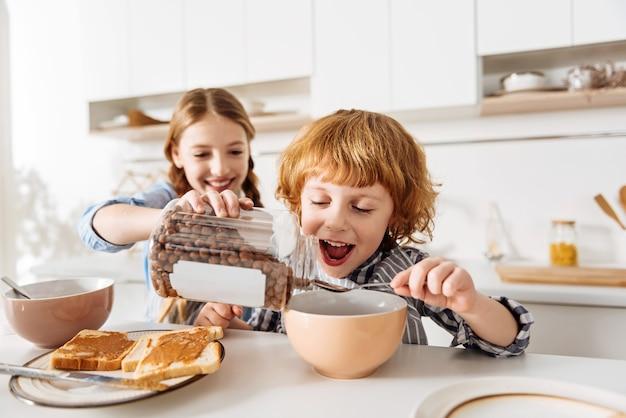 Geef mij meer. levendige, gepassioneerde vrolijke kinderen die er opgewonden uitzien voordat ze wat ontbijtgranen met chocoladesmaak eten terwijl zijn zus het in zijn kom giet Premium Foto