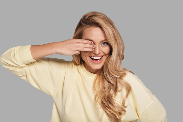 Geef nooit op! aantrekkelijke jonge glimlachende vrouw die het oog met de hand bedekt en naar de camera kijkt terwijl ze tegen een grijze achtergrond staat