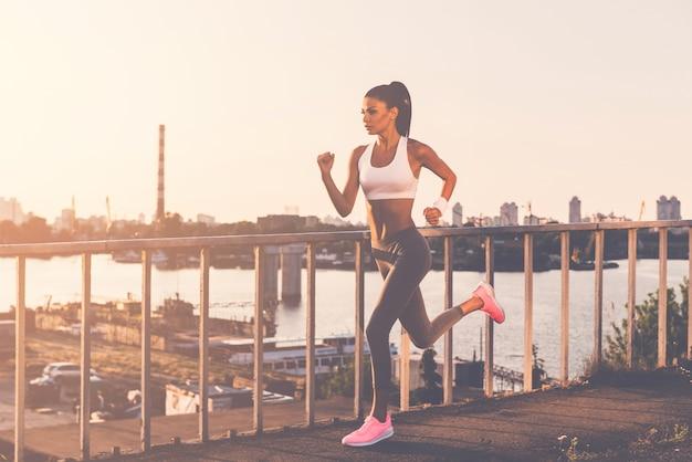 Geef nooit op en blijf in beweging! volledige lengte van mooie jonge vrouw in sportkleding