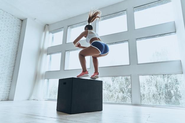 Geef nooit op. moderne jonge vrouw in sportkleding die springt tijdens het sporten in de sportschool