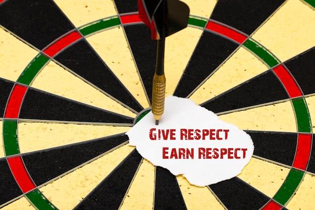 Geef respect verdien respect. darten met dartpijl die op een vel papier was gespeld voor labels
